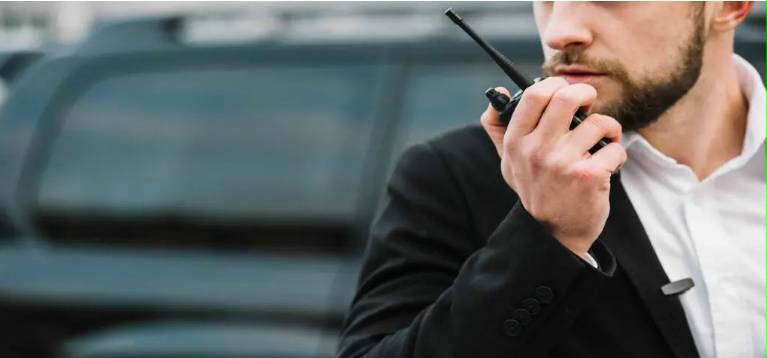 security guard notifying other guards during a mobile escort via a walky talky
