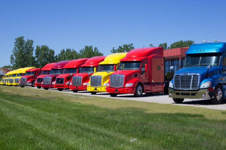 line of semitrucks resting at a trucking terminal