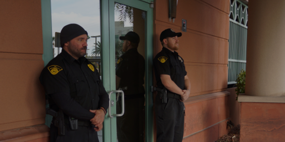 two armed guards outside of a client location